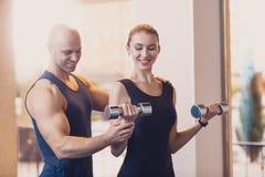Muchacha feliz que hace las manos de la pesa de gimnasia del ejercicio de la fuerza imagenes de archivo