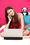 Muchacha feliz que hace una llamada y que usa su computadora portátil Foto de archivo
