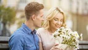 Muchacha feliz que huele las flores agradables, regalo del novio querido, fecha romántica Imagen de archivo libre de regalías
