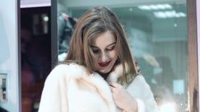 Muchacha feliz que intenta en y que presenta en abrigo de pieles en la tienda lentamente metrajes