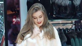 Muchacha feliz que intenta en y que presenta en abrigo de pieles en la tienda lentamente almacen de metraje de vídeo