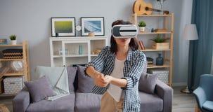 Muchacha feliz que juega al juego que lleva los vidrios de la realidad virtual en el apartamento solamente metrajes