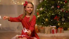 Muchacha feliz que juega con las bengalas en la Navidad almacen de metraje de vídeo