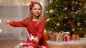 Muchacha feliz que juega con las bengalas en la Navidad almacen de video