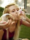 Muchacha feliz que juega con las burbujas de jabón Foto de archivo libre de regalías