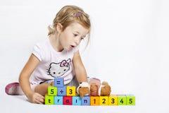 Muchacha feliz que juega con los bloques de madera coloridos Fotos de archivo
