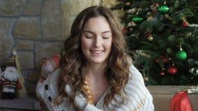 Muchacha feliz que juega con los regalos en el piso cerca del árbol de navidad lentamente almacen de video