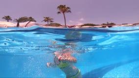 Muchacha feliz que juega en piscina al aire libre el vacaciones de verano en la playa tropical almacen de video