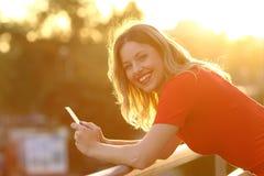 Muchacha feliz que le mira con un teléfono elegante la puesta del sol Foto de archivo