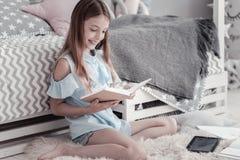 Muchacha feliz que lee un libro en el piso Fotografía de archivo libre de regalías