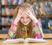 Muchacha feliz que lee un libro en la biblioteca Fotos de archivo libres de regalías