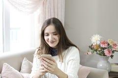 Muchacha feliz que lee un mensaje en un teléfono elegante que se sienta en un sofá en casa fotografía de archivo