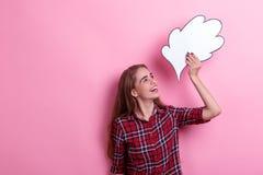 Muchacha feliz que lleva a cabo una imagen de papel del pensamiento o de la idea de arriba, sonriendo y mirándolo Fondo rosado Foto de archivo