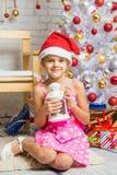 Muchacha feliz que lleva a cabo una vela en las manos que se sientan en una raspa de arenque del interior de los Años Nuevos Fotografía de archivo libre de regalías