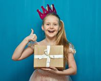 Muchacha feliz que lleva el pulgar rosado de la demostración de la caja de regalo de la tenencia del vestido y de la corona para  foto de archivo libre de regalías