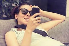 Muchacha feliz que manda un SMS en el teléfono elegante en un salón de la terraza del restaurante del hotel imágenes de archivo libres de regalías