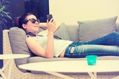 Muchacha feliz que manda un SMS en el teléfono elegante en un salón de la terraza del restaurante del hotel imagenes de archivo