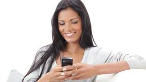 Muchacha feliz que manda un SMS a un mensaje con el teléfono almacen de metraje de vídeo