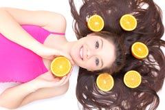Muchacha feliz que miente con los pedazos de naranja Imagenes de archivo