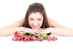 Muchacha feliz que miente con los tulipanes rosados Imagen de archivo libre de regalías