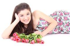 Muchacha feliz que miente con los tulipanes rosados Foto de archivo
