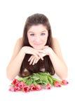 Muchacha feliz que miente con los tulipanes rosados Imágenes de archivo libres de regalías