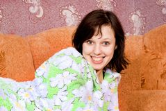 Muchacha feliz que miente en el sofá Foto de archivo libre de regalías