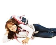 Muchacha feliz que miente en el suelo con el morral Fotografía de archivo