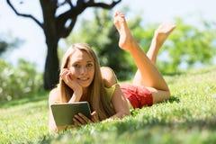 Muchacha feliz que miente en la hierba que goza leyendo el ereader Imagen de archivo
