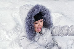 Muchacha feliz que miente en la nieve fotografía de archivo libre de regalías