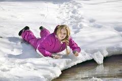 Muchacha feliz que miente en la nieve en invierno Imagen de archivo