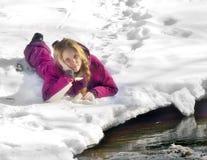 Muchacha feliz que miente en la nieve en invierno Fotos de archivo