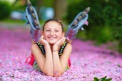 Muchacha feliz que miente en pétalos rosados, jardín del rodillo de la primavera Imagen de archivo