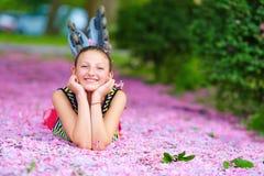 Muchacha feliz que miente en pétalos rosados, jardín del rodillo de la primavera Imágenes de archivo libres de regalías