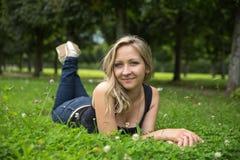 Muchacha feliz que miente en parque Imagen de archivo libre de regalías