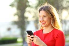 Muchacha feliz que mira el lado que sostiene un teléfono elegante Fotografía de archivo libre de regalías
