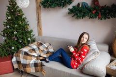 Muchacha feliz que mira fluyendo el contenido en línea en un teléfono elegante que se sienta en un sofá en invierno en casa Foto de archivo libre de regalías