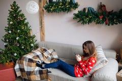 Muchacha feliz que mira fluyendo el contenido en línea en un teléfono elegante que se sienta en un sofá en invierno en casa Fotografía de archivo libre de regalías