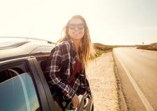 Muchacha feliz que mira hacia fuera la ventanilla del coche Foto de archivo