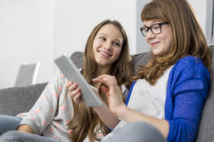 Muchacha feliz que mira a la hermana que usa la tableta digital en el sofá en casa Fotografía de archivo libre de regalías