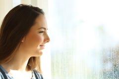 Muchacha feliz que mira a través de una ventana después de la lluvia Foto de archivo libre de regalías