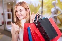 Muchacha feliz que muestra como el gesto para hacer compras Fotografía de archivo