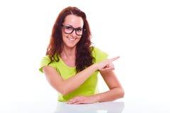 Muchacha feliz que muestra el finger en un espacio en blanco Foto de archivo libre de regalías