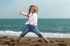Muchacha feliz que muestra los pulgares para arriba en la playa Imágenes de archivo libres de regalías