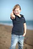 Muchacha feliz que muestra los pulgares para arriba en la playa Fotografía de archivo libre de regalías