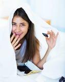 Muchacha feliz que oculta debajo de la hoja con los dulces dentro Fotos de archivo