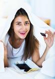Muchacha feliz que oculta debajo de la hoja con los dulces dentro Foto de archivo