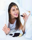 Muchacha feliz que oculta debajo de la hoja con los dulces dentro Imagenes de archivo