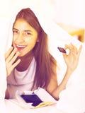 Muchacha feliz que oculta debajo de la hoja con los dulces dentro Imágenes de archivo libres de regalías