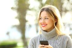 Muchacha feliz que parece ausente y que sostiene el teléfono en invierno Fotografía de archivo
